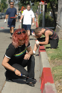 Angela Parry paints the curb red between no-parking signs on Rayen Street.  Northridge Community Neighborhood Watch took to the streets to paint curbs and clean up trash near the corner of Rathburn and Rayen streets in Northridge. Northridge, Ca 7-30-2011. (John McCoy/Staff Photographer)