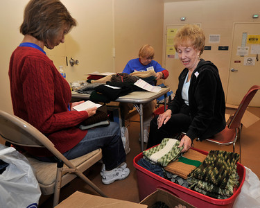 (l-r) Elaine Campbell, Lorene Van Arch-Miller and Donna Rothman sort through scarves and hats.  Operation Gratitude is a nonprofit organization that gathers donated goods and assembles care packages to send to servicemen and women overseas. Over Thanksgiving weekend, they'll be working in high gear to get the packages in the mail for the Christmas holidays. This year, Operation Gratitude asked for hand-knitted and crocheted scarves to include in each package to the troops would receive something personal. Van Nuys, CA.11-26-2010. (John McCoy/staff photographer)