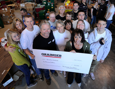 Industrial supply company Grainger donated $10,000.00 to help keep the care packages moving. Operation Gratitude volunteers are assembling holiday care packages for troops who are away from home during the holidays. Hundreds of volunteers packed the National Guard Armory at 17330 Victory Blvd. to pack boxes with items like books, CD's, candy, beanie babies and a knit cap or scarf. Van Nuys, CA 11/26/2011(John McCoy/Staff Photographer)