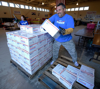 Chris Pulos stacks care packages on a pallet. Operation Gratitude volunteers are assembling holiday care packages for troops who are away from home during the holidays. Hundreds of volunteers packed the National Guard Armory at 17330 Victory Blvd. to pack boxes with items like books, CD's, candy, beanie babies and a knit cap or scarf. Van Nuys, CA 11/26/2011(John McCoy/Staff Photographer)