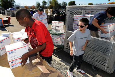 (l-r) Leonard Taylor and Lewis Tachau load care packages into a shipping container. Operation Gratitude volunteers are assembling holiday care packages for troops who are away from home during the holidays. Hundreds of volunteers packed the National Guard Armory at 17330 Victory Blvd. to pack boxes with items like books, CD's, candy, beanie babies and a knit cap or scarf. Van Nuys, CA 11/26/2011(John McCoy/Staff Photographer)