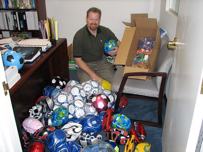 Shane Harkins in his Marsh Private Client Services business Woodland Hills, Ca. office with donated soccer balls that are collected and sent to be distributed to Afghan children.