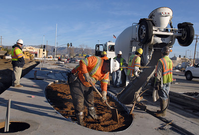 Workers pour colored concrete into decorative oval shapes.  The Orange Line Busway extension from Canoga Park to Chatsworth, CA. is expected to be compleated months ahead of schedule and $30 million under budget.  Thursday, December 29. 2011.  (Dean Musgrove/Staff Photographer)