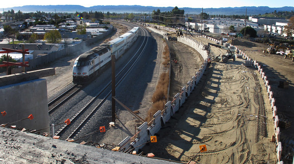 Workers build a wall on the approach to the bridge over Lassen Street as a Metrolink train passes by.  The Orange Line Busway extension from Canoga Park to Chatsworth, CA. is expected to be compleated months ahead of schedule and $30 million under budget.  Thursday, December 29. 2011.  (Dean Musgrove/Staff Photographer)