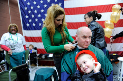 LAFD firefighter Rob Curtis has his head shaved by hairdresser Letti Magana, as son Nicholas, 4-years-old, watches during the St. BaldrickÕs Foundation Head-Shaving Event at LAFD Fire Station 89 in North Hollywood Saturday, March 17, 2012. The event was anticipated to raise $100,000 with more than 200 participants registered with proceeds going to children's cancer. (Hans Gutknecht/Staff Photographer)