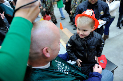 LAFD firefighter Rob Curtis has his head shaved as son Nicholas, 4-years-old, watches during the St. BaldrickÕs Foundation Head-Shaving Event at LAFD Fire Station 89 in North Hollywood Saturday, March 17, 2012. The event was anticipated to raise $100,000 with more than 200 participants registered with proceeds going to children's cancer. (Hans Gutknecht/Staff Photographer)