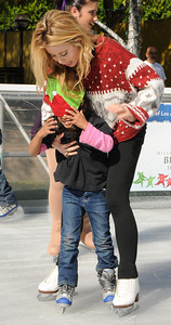 Olympic Champion figure skater Tara Lipinski helps 5-year-old Anayeli Morales as she struffles with the ice and her hat. Pershing Square has been transformed into a partial winter wonderland as the 14th annual Downtown On Ice Holiday Rink was opened Thursday Morning, 11/17/2011.  Olympic Champion Tara Lipinski, Mayor Antonio Villaraigosa, a skating Snoopy and girls from the Los Angeles Ice Theater Youth Ensemble welcomed Children from San Pedro Street Elementary and Sheenway School and Cultural Center to be the first to take to the ice for the holiday season. The rink will be open everyday, including holidays through January 16, 2012. The charge to skate is $6 plus an additional $2 if you need to rent skates. Los Angeles, CA. 11/17/2011(John McCoy/Staff Photographer)