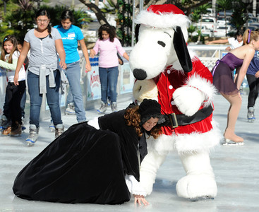 Sharilyn Christensen gets help from Snoopy after a fall. Pershing Square has been transformed into a partial winter wonderland as the 14th annual Downtown On Ice Holiday Rink was opened Thursday Morning, 11/17/2011.  Olympic Champion Tara Lipinski, Mayor Antonio Villaraigosa, a skating Snoopy and girls from the Los Angeles Ice Theater Youth Ensemble welcomed Children from San Pedro Street Elementary and Sheenway School and Cultural Center to be the first to take to the ice for the holiday season. The rink will be open everyday, including holidays through January 16, 2012. The charge to skate is $6 plus an additional $2 if you need to rent skates. Los Angeles, CA. 11/17/2011(John McCoy/Staff Photographer)