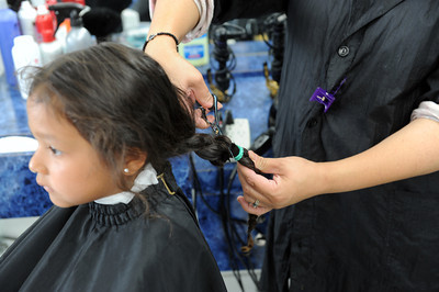 Hairdresser Puresa Hernandez cuts off Maya Contreras'  ponytail at  Latina beauty in San Fernando. Maria Carrillo is hoping to collect 100 donations of ponytails that will make a wig for those with cancer. So far she has 70 collected mostly from Morningside Elementary School students. (Hans Gutknecht/Staff Photographer)