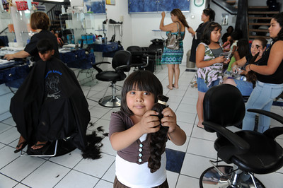 Monserrath Marcial, 8-years-old, holds her ponytail at at Estetica Latina beauty in San Fernando. Marcial who is being treated for leukemia inspired Maria Carrillo to collect 100 donations of ponytails that will make a wig for those with cancer. So far she has 70 collected mostly from Morningside Elementary School students. (Hans Gutknecht/Staff Photographer)