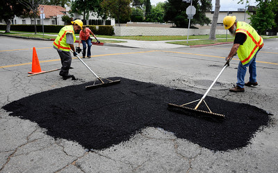LA city workers fix one of the many potholes near Van Nuys high school, as LA mayor Antonio Villaraigosa talks about the major pothole project on the way in the city and valley for repairs. Van Nuys CA.  June 6,2011. Photo by Gene Blevins/LA DailyNews