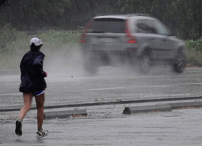 A jogger runs through the heavy bands of rain moved across Los Angeles County, and triggered warnings from the National Weather Service of possible localized ponding and flooding across the Southland.  Van Nuys CA.March 25.2012. Photo by Gene Blevins/LA Daily News