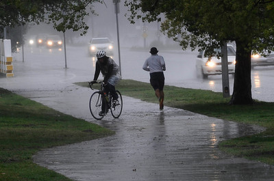 Joggers and bikers runs through the heavy bands of rain moved across Los Angeles County, and triggered warnings from the National Weather Service of possible localized ponding and flooding across the Southland.  Van Nuys CA.March 25.2012. Photo by Gene Blevins/LA Daily News