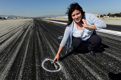 Diana Sanchez, Public and Community Relations Director for Van Nuys Airport, shows an area on Runway 16 Right that has damage. Van Nuys Airport is planning to shut down its one runway for as much as two months next year to rebuild the badly damaged strip of asphalt. Local businesses and airport tenants are pushing LAWA to do a patch job instead so the runway wonÕt have to close. Van Nuys, CA 3/20/2012(John McCoy/Staff Photographer)