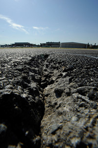 This closeup photo with a wide angle lens shows one of the large cracks in the 16 Right runway where loose chunks of asphalt become a hazard to aircraft. Van Nuys Airport is planning to shut down its one runway for as much as two months next year to rebuild the badly damaged strip of asphalt. Local businesses and airport tenants are pushing LAWA to do a patch job instead so the runway won't have to close. Van Nuys, CA 3/20/2012(John McCoy/Staff Photographer)