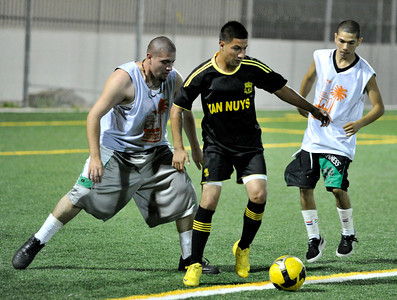 A Barrio Van Nuys player works his way between two Vineland Boys. A soccer match between Sun Valley Parks Vineland Boys, and Delano Parks, Barrio Van Nuys, was played at Delano Park during the Summer Night Lights program. The rival gangs decided to leave their differences behind them, and play a spirited game of soccer.  Van Nuys CA. 8-24-2011. (John McCoy/Staff Photographer)