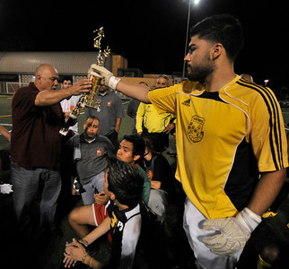 Event organizer Blinky Rodriguez hands a throphy to Barrio Van Nuys goalie Robert Lopez. A soccer match between Sun Valley Parks Vineland Boys, and Delano Parks, Barrio Van Nuys, was played at Delano Park during the Summer Night Lights program. The rival gangs decided to leave their differences behind them, and play a spirited game of soccer.  Van Nuys CA. 8-24-2011. (John McCoy/Staff Photographer)