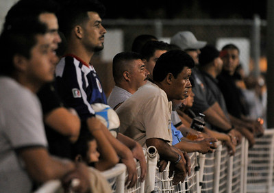 Spectators along the sideline watch the gang members compete. A soccer match between Sun Valley Parks Vineland Boys, and Delano Parks, Barrio Van Nuys, was played at Delano Park during the Summer Night Lights program. The rival gangs decided to leave their differences behind them, and play a spirited game of soccer.  Van Nuys CA. 8-24-2011. (John McCoy/Staff Photographer)