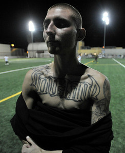A Vineland Boy shows off the ink on his chest. A soccer match between Sun Valley Parks Vineland Boys, and Delano Parks, Barrio Van Nuys, was played at Delano Park during the Summer Night Lights program. The rival gangs decided to leave their differences behind them, and play a spirited game of soccer.  Van Nuys CA. 8-24-2011. (John McCoy/Staff Photographer)
