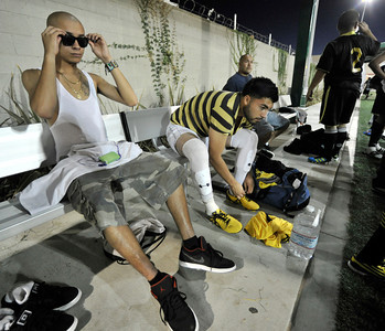 (l-r) Barrio Van Nuys players Jesus Ramirez and Robert Lopez adjust their equipment before the game. A soccer match between Sun Valley Parks Vineland Boys, and Delano Parks, Barrio Van Nuys, was played at Delano Park during the Summer Night Lights program. The rival gangs decided to leave their differences behind them, and play a spirited game of soccer.  Van Nuys CA. 8-24-2011. (John McCoy/Staff Photographer)