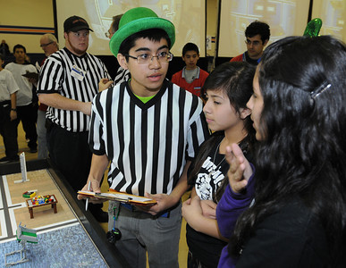 Robotics judge Gabriel Ruiz,16, talks to contestants Emely Zeledon,13, and Nancy Perez,13, who are from Wilmington Middle School in Wilmington, CA.  Chaminade College Preparatory Middle School hosted the LEGO league Food Factor Challenge. The idea was to use robotics and LEGOÕs to inspire creative thinking in food safety research. Kids dressed  up in costumes, and programmed computer vehicles to automatically drive a field and move objects. Chatsworth, CA 12/16/2011(John McCoy/Staff Photographer)