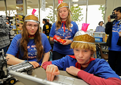 (l-r) Sierra Lien,14, and Hannah Schaffner,13, watch as Matthew Koonce,13, works on a computer program that will help their robot run an obstical course. The kids are from Joe Walker Middle School in Lancaster. Chaminade College Preparatory Middle School hosted the LEGO league Food Factor Challenge. The idea was to use robotics and LEGO's to inspire creative thinking in food safety research. Kids dressed  up in costumes, and programmed computer vehicles to automatically drive a field and move objects. Chatsworth, CA 12/16/2011(John McCoy/Staff Photographer)