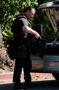 LAPD SWAT arrive at the scene were four armed gunman this afternoon who robbed two businesses and fired at a witness who pursued them into Sherman Oaks. Two additional suspects remain at large. Officers cordoned off three square blocks of Sherman Oaks as they searched for the four suspected gunmen, catching two of them later in the afternoon. The first robbery was reported about 1:45 p.m. in an industrial section near Saticoy Street and Haskell Avenue in Van Nuys. The suspects  ran into the neighborhood south of Ventura Boulevard and west of the 405 Freeway, abandoning a vehicle Two of the four suspects have been caught and are described only as African-American men. Sherman Oaks Ca. Aug 8,2011 photo by Gene Blevins/LA DailyNews