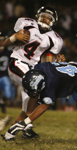 Arleta's  Noe Cardenas gets tackled by Sylmar's Angel Anguiano during the game on Friday, September 7, 2007 (Edna T. Simpson)