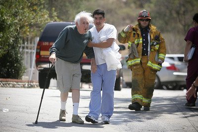 HOSPITAL FIRE--A patients is evacuated to the parking lot after a roof fire broke out at the Santa Clarita Convalescent Hospital shortly after 2pm.  Firefighters found a roof fire when they arrived on the scene and evacuations were under way.  About 100 patients were evacuated in the fire.  TO GO WITH ADOB STORY.    Photo by David Crane/Staff Photographer.