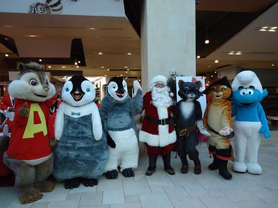 Aaron Gamez poses with a gaggle of characters at Santa Walk 2011 at Westfield Shoppingtown Topanga.