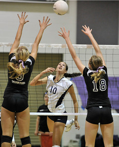 """Saugus #10 Jaclyn Clark tips the ball up high over the net and past Valencia #9 Sydney Striff and """"#18 Lindsey Knudsen. The Valencia Girls volleyball team hosted Saugus in a Foothill League game. Saugus won in 3 straight games. Valencia, CA 9/27/2011(John McCoy/Staff Photographer)"""