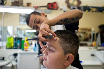 Mario Jimenez cuts the hair of 9-year-old Leo Castaneda on Friday, Aug. 19, 2011 at Joe's Barbershop on Ventura Boulevard in Tarzana, Calif. Castaneda had the idea for Jiminez to shave a star on the left side of his head.  (Maya Sugarman/Staff Photographer)