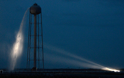 Water spills out of the water tower as Space shuttle Atlantis sits on the pad as all systems are go with only the weather that could delay todays launch from Kennedy Space Center. FL. July 7,2011. Photo by Gene Blevins/LA Daily News