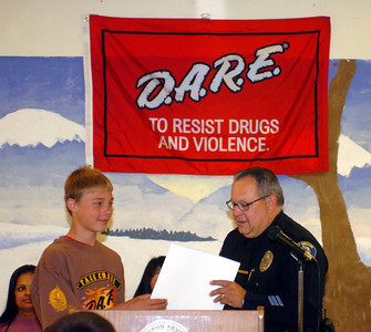 D.A.R.E. graduate Cameron Mason, a 6th grader at Atherwood Elementary School in Simi Valley receives an award from Simi Valley Police Officer, Don Anderson, for his essay about not doing drugs on Friday, June 1, 2007.  (Tina Burch/Staff Photographer)