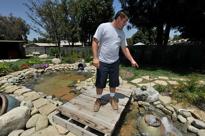 """Anthony Cassella stands on the bridge over his water feature.  Cassella's backyard got the """"Gentleman's Ranch""""-treatment from Billy Derian, host of DIY Network's Extra Yardage: a half-hour landscaping series in which neglected decks, patios and yards are transformed into world-class outdoor entertainment spaces. The yard will be featured in an upcoming episode of the series. Simi Valley Ca 7-29-2011. (John McCoy/Staff Photographer)"""