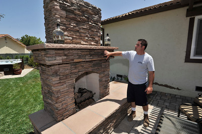 """Anthony Cassella looks at his new fireplace. Cassella's backyard got the """"Gentleman's Ranch""""-treatment from Billy Derian, host of DIY Network's Extra Yardage: a half-hour landscaping series in which neglected decks, patios and yards are transformed into world-class outdoor entertainment spaces. The yard will be featured in an upcoming episode of the series. Simi Valley Ca 7-29-2011. (John McCoy/Staff Photographer)"""