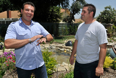 """(l-r) Billy Derian and Anthony Cassella stand next to a water feature in Cassella's backyard that got the """"Gentleman's Ranch""""-treatment from Derian, host of DIY Network's Extra Yardage: a half-hour landscaping series in which neglected decks, patios and yards are transformed into world-class outdoor entertainment spaces. The yard will be featured in an upcoming episode of the series. Simi Valley Ca 7-29-2011. (John McCoy/Staff Photographer)"""