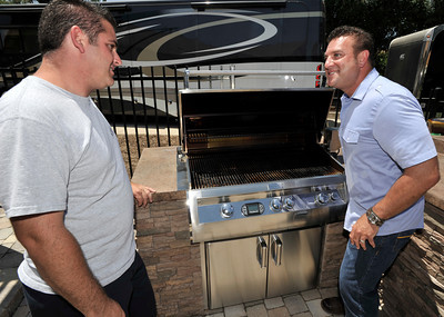 """Anthony Cassella proves to Billy Derian that he does, in fact, use his BBQ. Cassella's backyard got the """"Gentleman's Ranch""""-treatment from Derian, host of DIY Network's Extra Yardage: a half-hour landscaping series in which neglected decks, patios and yards are transformed into world-class outdoor entertainment spaces. The yard will be featured in an upcoming episode of the series. Simi Valley Ca 7-29-2011. (John McCoy/Staff Photographer)"""