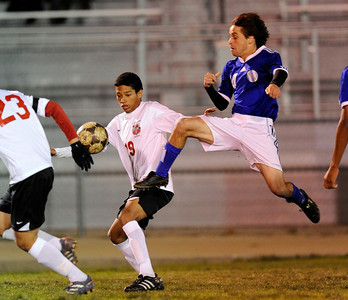 El Camino Real's Lucas Ladek (14) kicks the ball away from Cleveland'sEdgar Hernandez (19) during their game at Cleveland High School in Reseda Friday, January 13, 2011.  (Hans Gutknecht/Staff Photographer)