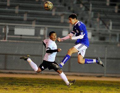 El Camino Real's  Osvaldo Martinez (2) gets the ball past Cleveland's Helio Deleon (11) during their game at Cleveland High School in Reseda Friday, January 13, 2011.  (Hans Gutknecht/Staff Photographer)