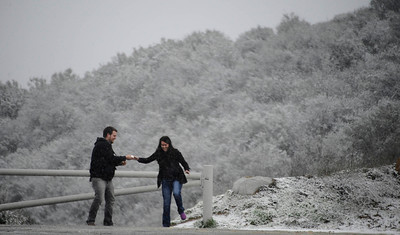 A couple collects snowballs from the heavy snow fall above Castaic Lake that covered the Newhall pass to Santa Clarita and the Grapevine as residents were treated to an early 2011 snowfall Sunday afternoon after a light rain turned to flurries and then to a heavy snowfall. Castaic Lake CA. Jan 2,2011 Photo by Gene Blevins/LA DailyNews