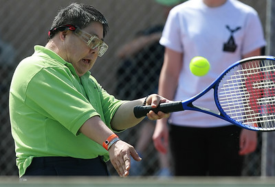 Teddy Yoshida of the South Bay tennis team returns the ball toward his opponent from the Greater Los Angeles team during one of many tennis games on the courts at Hart High School where nearly 800 Special Olympics athletes from all  over Southern California ages 8-80 with Down's Syndrome, autism  and mild retardation competed in basketball, bocce, swimming, track and field, and tennis in Newhall, CA, on Saturday, May 19, 2007.  ( John Lazar/L.A. Daily News Staff Photographer )