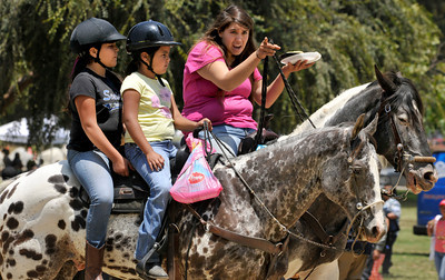 """(l-r) Fernando Silis,9, Brianna Villasenor,7, and Cassandra Villega look for a place to park their horses so that they can eat their tacos. On Saturday July 3, 2010, churches, ministries and the community will gathered together to celebrate the """"Uplifting of the American Spirit"""" at Hansen Dam. The  offered a family celebration of the Fourth. Each church will hold an old fashioned church picnic with its congregation, families and friends in an atmosphere of relaxation. Additionally, the audience listened to inspirational music while taking advantage of the fishing and swimming lakes as well as other wholesome outdoor activities available at Hansen Dam. Lakeview Terrace, CA 07/03/2010 (John McCoy/Staff Photographer)"""