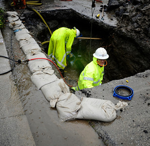 DWP had to use sandbags to keep water out as they work in holds to repair broken water pipes during the heavy rain storm that came through the valley that caused major flooding and blown down trees. March 20,2011. Sherman Oaks Photo by Gene Blevins/LA Daily News
