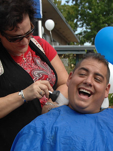 Eileen Solomon puts powder on Manny Villanuevas neck. Students at Madison Middle School in North Hollywood were challenged by their Assistant Principal, Bill Hedrick, and Dean, Justin Lauer, and Security Officer Manny Villanueva, to improve thier API Scores above the 690 mark. They promised to shave their heads into mohawks during a school assembly if they were successful. The students improved from 671 to 704, smashing the old score by 33 points. Hair Dresser Eileen Solomon brought her clippers, and gave the haircuts during an assembly in front of the entire school. North Hollywood , CA 9/31/2010 (John McCoy/staff photographer)