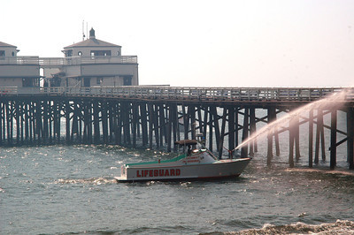 An LA County lifeguard boat hoses down the pilings at the Malibu Pier  to keep burning embers from starting a fire on the famed structure.  Photo by Mike Meadows/Special to the Daily News.