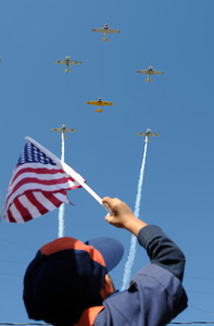 Tiger Cub Scout Dong Jun,6, waves his flag at vintage military aircraft that flew over the Veterans Day Parade route. November 11, 2011, Councilmember Richard Alarcón will hosted the Eighth Annual San Fernando Valley Veterans Day Parade, a tradition that was started in 2004. This year, Councilmember Alarcón is working with Congressman Berman, Commissioner Fred Flores, the San Fernando Valley Veterans Day Parade Committee and members of the San Fernando Valley community to host the event.  The parade will involve more than 120 veterans groups and numerous high school marching bands and each wartime era since World War II will be specifically represented in the parade. Sylmar, CA. 11/11/2011(John McCoy/Staff Photographer)