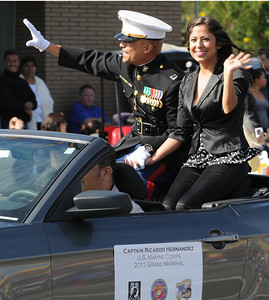 Grand Marshal of the veterans parade USMC Captain Ricardo Hernandez and his wife Fabiola wave to the crowd. November 11, 2011, Councilmember Richard Alarcón will hosted the Eighth Annual San Fernando Valley Veterans Day Parade, a tradition that was started in 2004. This year, Councilmember Alarcón is working with Congressman Berman, Commissioner Fred Flores, the San Fernando Valley Veterans Day Parade Committee and members of the San Fernando Valley community to host the event.  The parade will involve more than 120 veterans groups and numerous high school marching bands and each wartime era since World War II will be specifically represented in the parade. Sylmar, CA. 11/11/2011(John McCoy/Staff Photographer)
