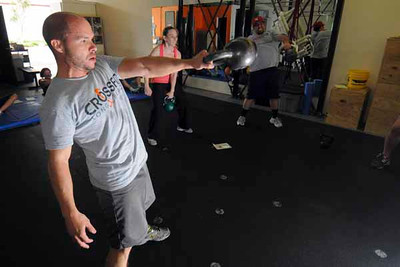 LONG BEACH - 04/24/2010 - (Scott Varley/Daily Breeze) People take part in a Tabata workout at CrossFit Long Beach. Tabata is a workout method where participants exercise at intense levels for 20 seconds followed by 10 seconds of rest for 8 cycles.  Carlos Cueva and others toss a heavy kettle bell above his head. He must do as many reps as he can in the 20 second intervals.