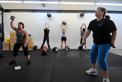 LONG BEACH - 04/24/2010 - (Scott Varley/Daily Breeze) People take part in a Tabata workout at CrossFit Long Beach. Tabata is a workout method where participants exercise at intense levels for 20 seconds followed by 10 seconds of rest for 8 cycles.  As one group tosses 16-pound medicine balls up to a line on the wall, another group works out with kettle bells.